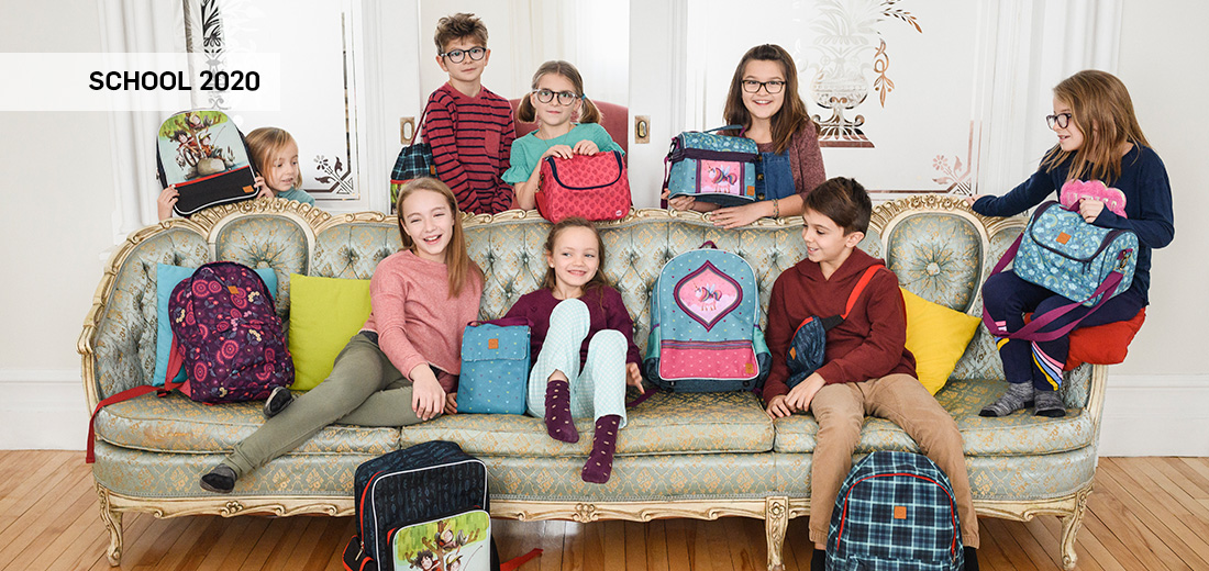 Kids sitting on a sofa with backpacks and lunch bags