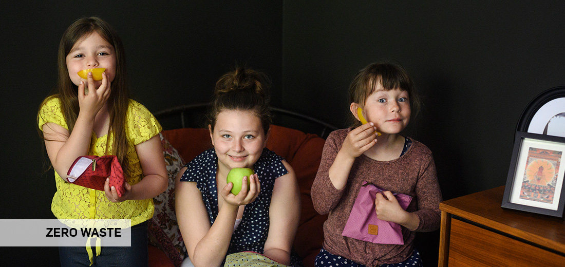 Girls holding zero waste pouches and food